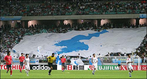 대형 한반도기가 관중석을 뒤덮은 가운데 남북 선수들이 경기를 벌이고 있다. 대형 한반도기가 관중석을 뒤덮은 가운데 남북 선수들이 경기를 벌이고 있다.